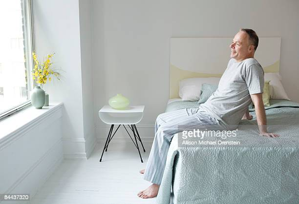 man sitting on edge of bed smiling