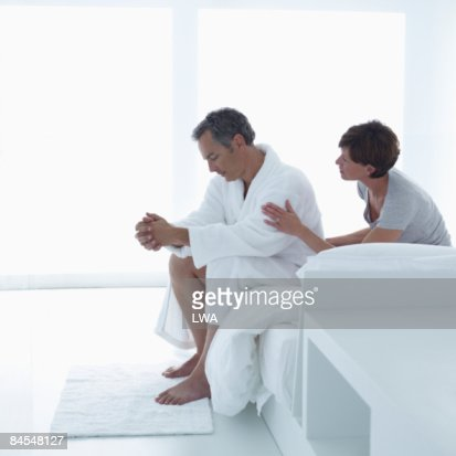 Man Sitting on Edge of Bed, Wife Consoling Him : Stock Photo