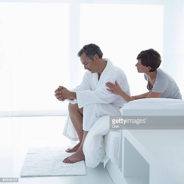 Man Sitting on Edge of Bed, Wife Consoling Him
