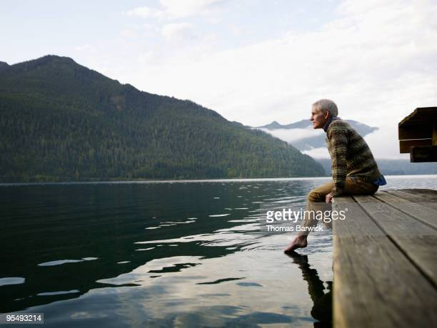 Man sitting on edge of dock with feet in water