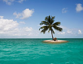 Man sitting on edge of small island with one palm tree