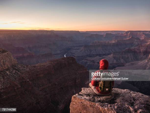 Man sitting on edge of South Rim, Grand Canyon National Park looking out at sunset, Arizona, USA
