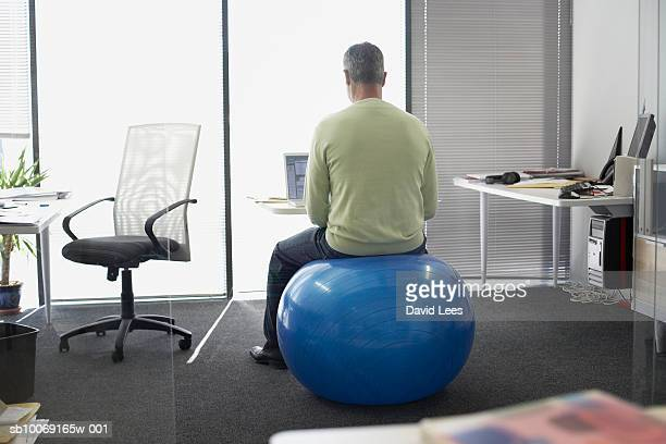 Man sitting on fitness ball working in office, rear view