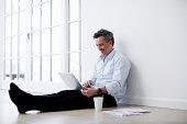 Man sitting on floor sing laptop