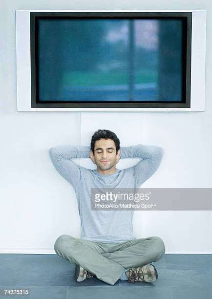 Man sitting on floor under wide screen TV, hands behind head and eyes closed