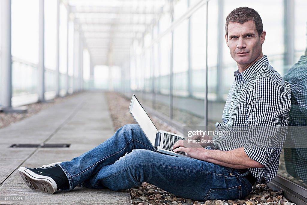 Man sitting on floor using laptop : Stock Photo