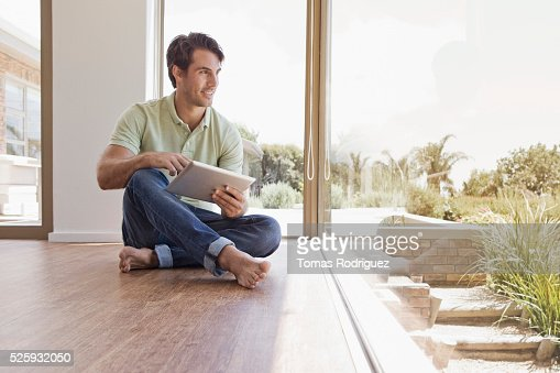Man sitting on floor using tablet pc : Stockfoto