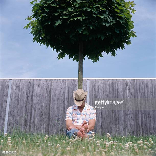 Man Sitting on Grass Leaning Against Tree Sleeping