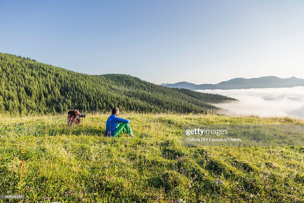 Man sitting on grass looking at view, Tyrol, Austria : Stock Photo