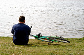 Man sitting on grassy bank overlooking lake, with bicycle laying beside him