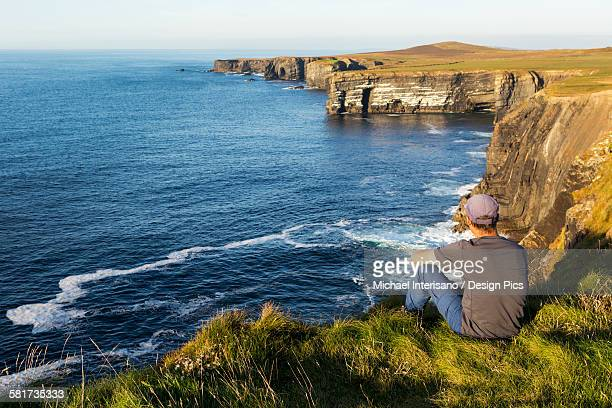 Man sitting on grassy cliff edge overlooking the dramatic rock cliffs along the shoreline at sunset
