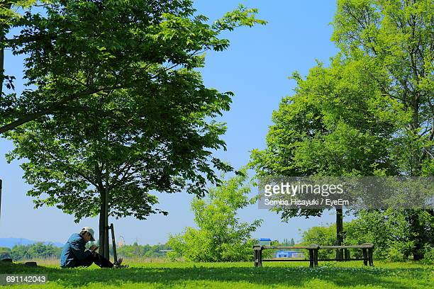 Man Sitting On Grassy Field A Park