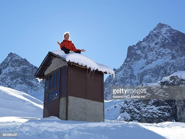 Man sitting on hut roof, practicing yoga.