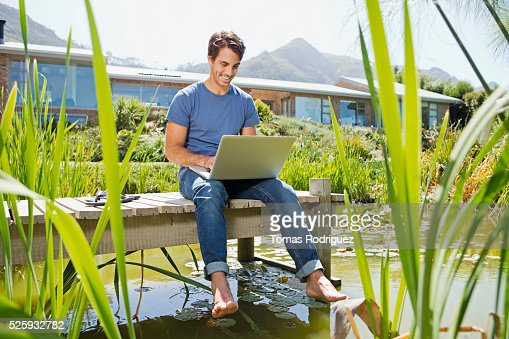 Man sitting on jetty and using laptop : Foto de stock