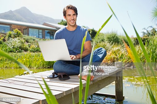 Man sitting on jetty and using laptop : Stockfoto