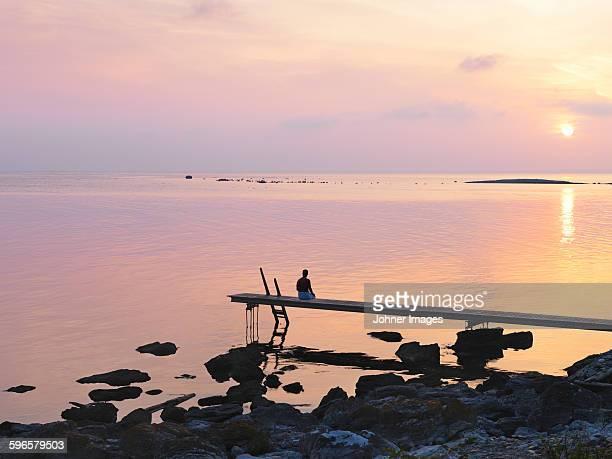 Man sitting on jetty at sunset