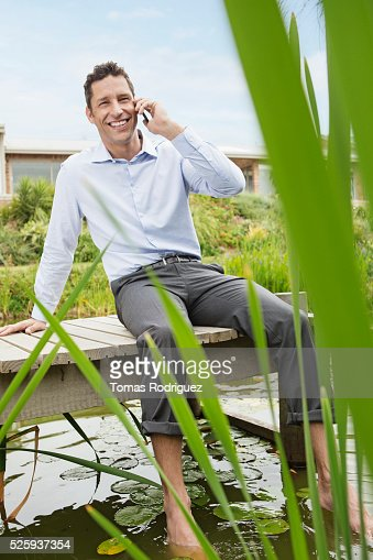 Man sitting on jetty by pond and talking on cell phone : Stock Photo