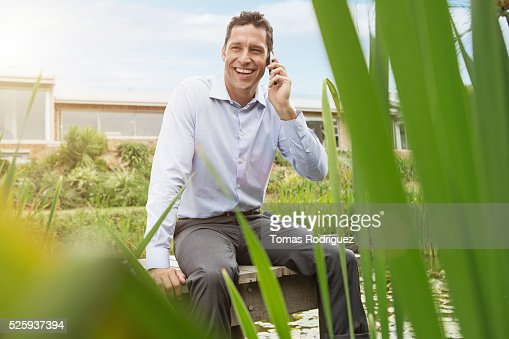 Man sitting on jetty by pond and talking on cell phone : Stockfoto