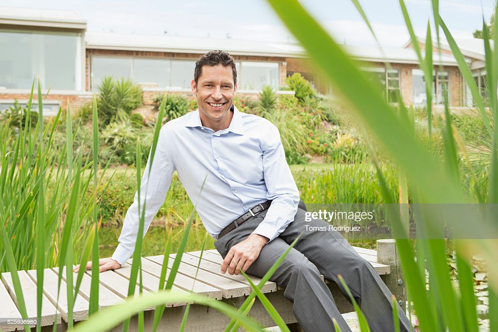 Man sitting on jetty by pond in back yard : Stock Photo