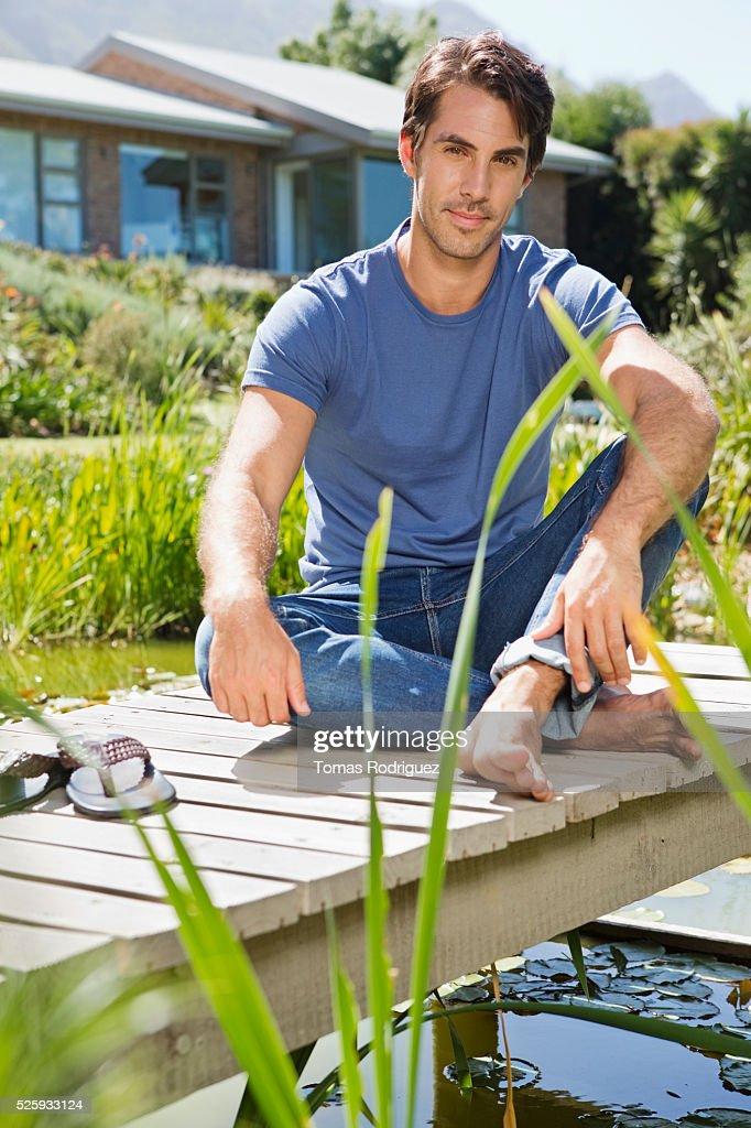 Man sitting on jetty : Stock Photo