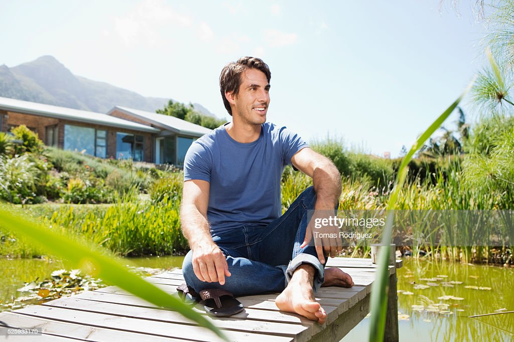 Man sitting on jetty : ストックフォト