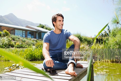 Man sitting on jetty : Foto de stock