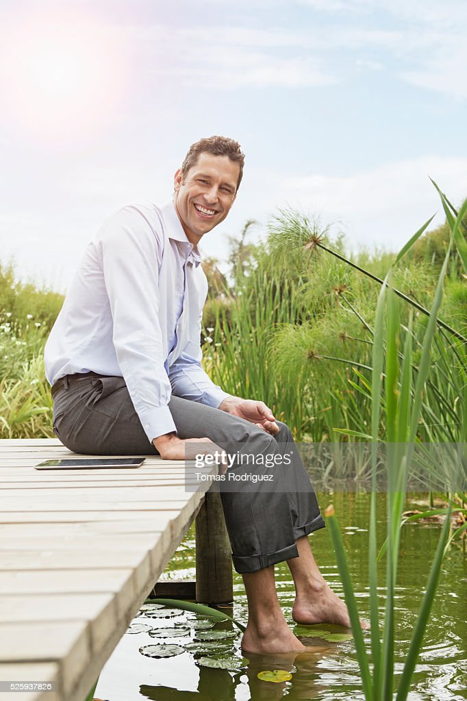 Man sitting on jetty with digital tablet : Stock-Foto