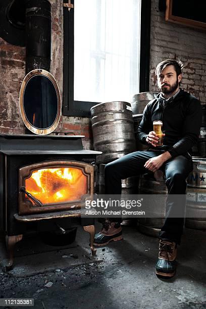 Man sitting on keg drinking beer near fireplace
