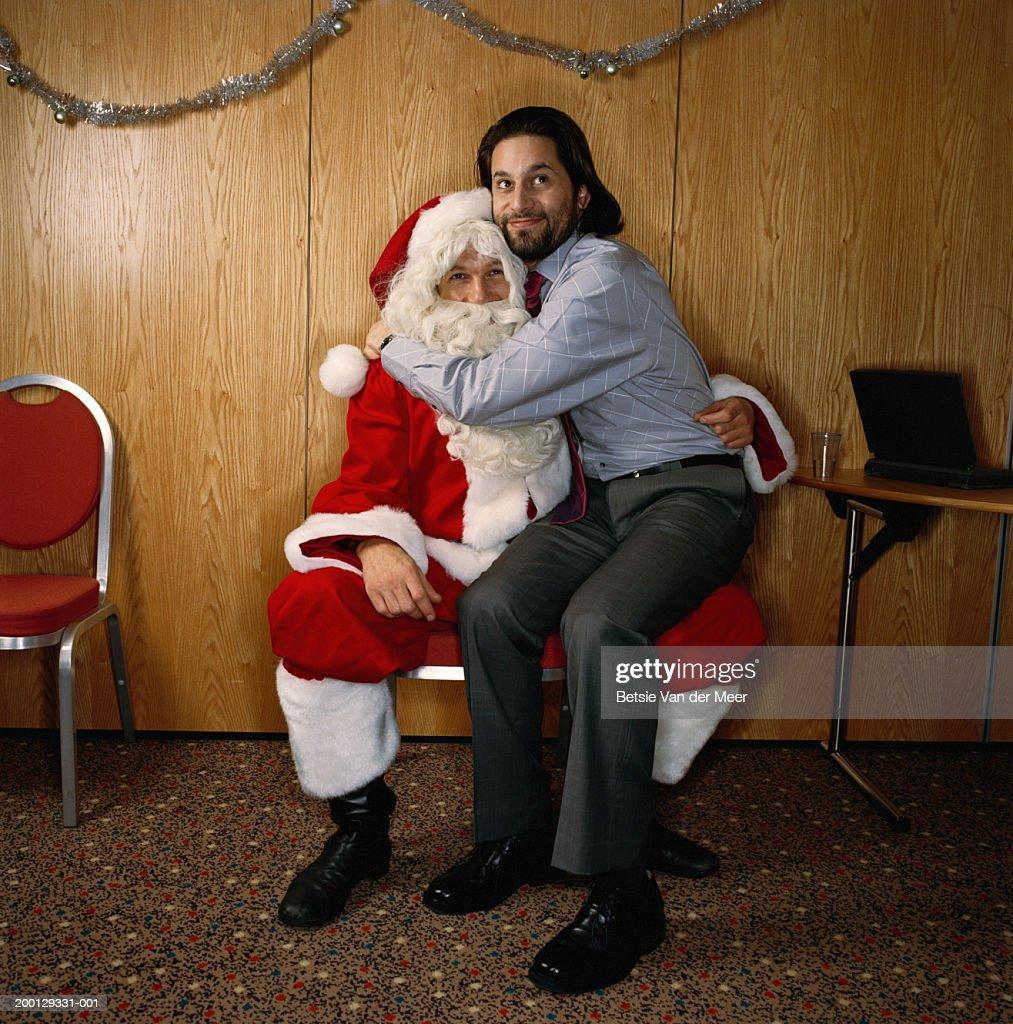 Man sitting on knee of man dressed as Santa : Stock Photo