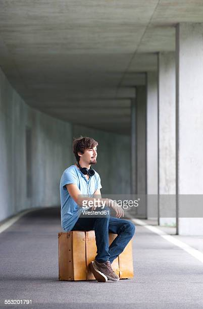 Man sitting on leather suitcase in a car park