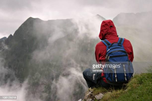 Mann sitzt auf Sims und Blick in die Berge