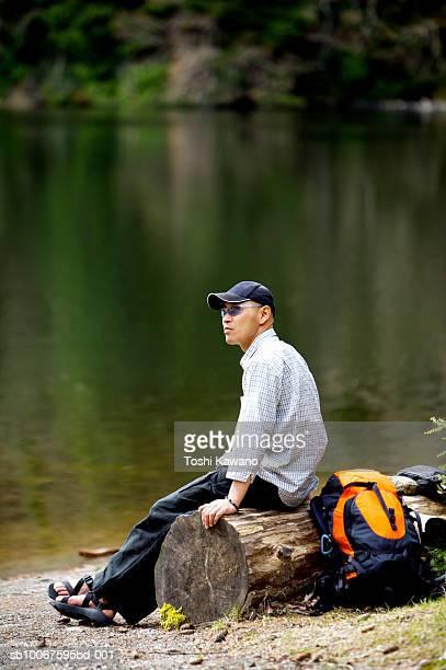 Man sitting on log by lake