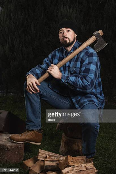 Man sitting on log holding an axe