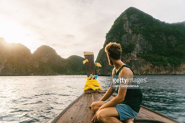 Man sitting on long tail boat