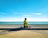 Back view of young skater sitting and relaxing on longboard or skateboard on beach at sea and blue sky background