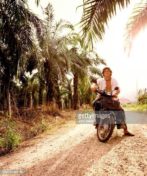 Man sitting on motorbike on palm lined dirt track