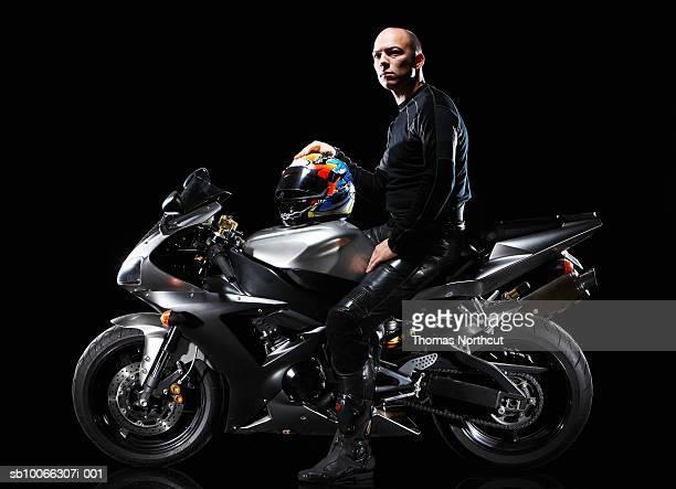 Man sitting on motorbike, side view