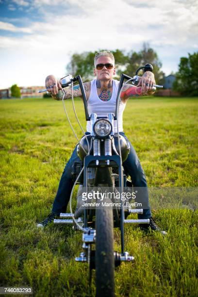 Man Sitting On Motorcycle At Grassy Field Against Sky