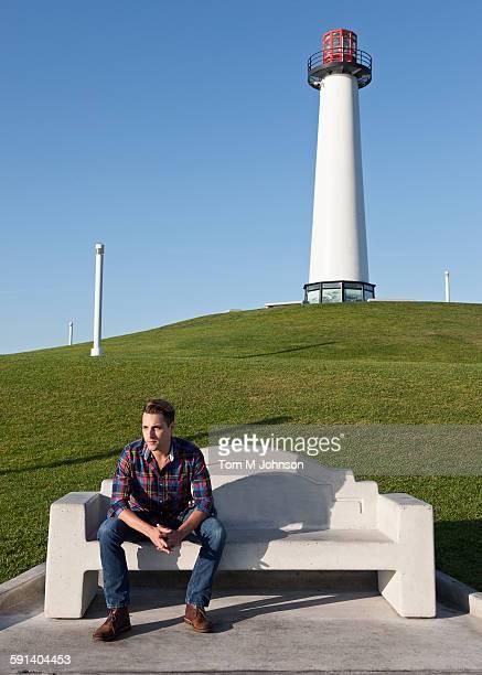 Man sitting on park bench near lighthouse