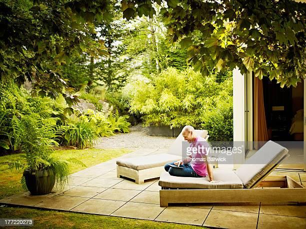 Man sitting on patio working on digital tablet