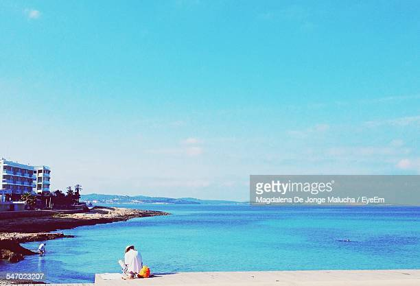 Man Sitting On Pier With Blue Sea In Background