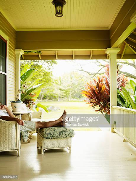 Man sitting on porch of tropical home feet up