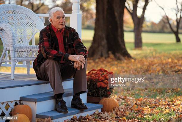 Man sitting on porch stairs on an autumn day