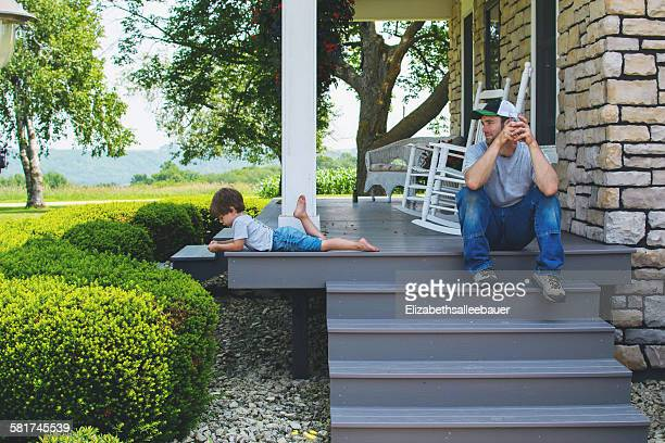 Man sitting on porch steps looking at son