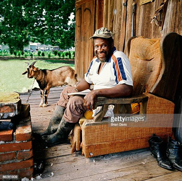 Man sitting on porch with his pet goat in the background
