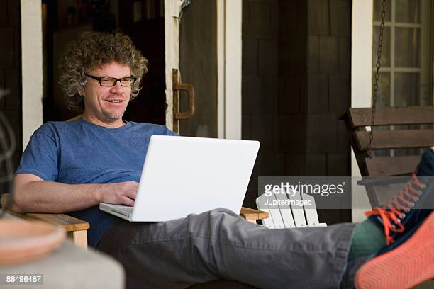 Man sitting on porch with laptop computer