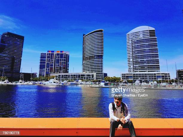 Man Sitting On Retaining Wall Against Lake In City
