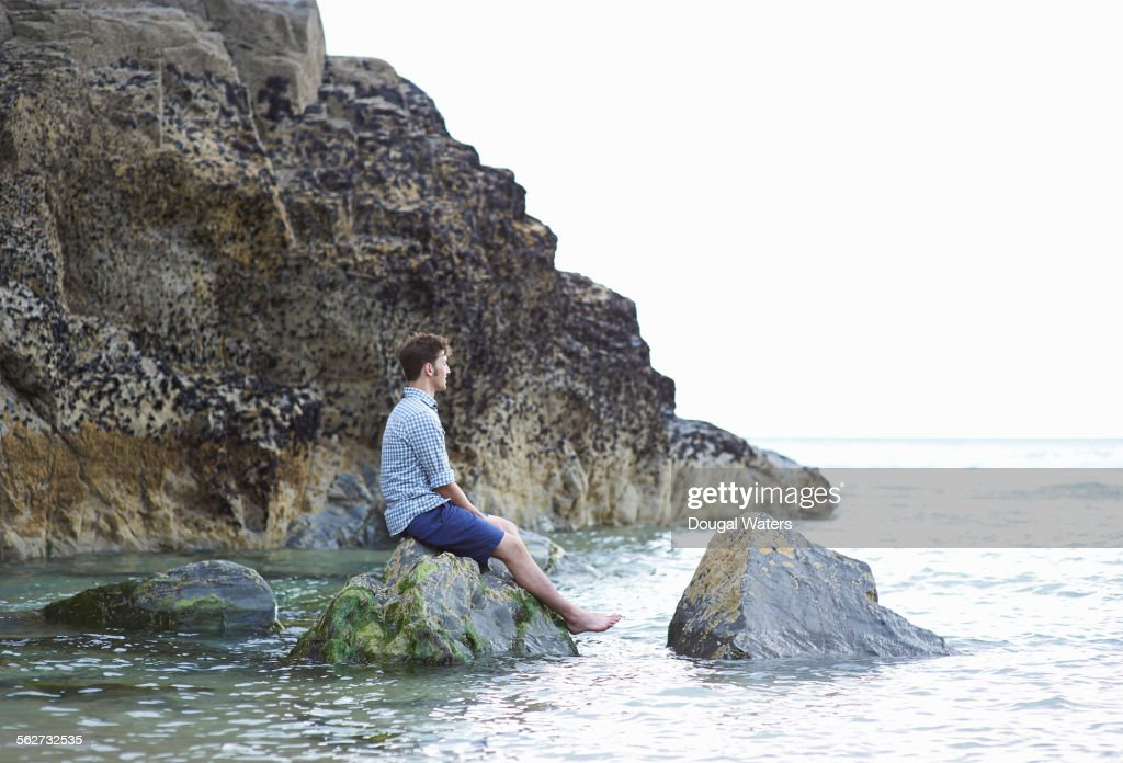 Man sitting on rock and looking out to sea