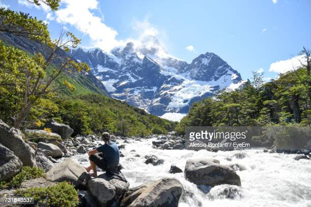 Man Sitting On Rock By River Flowing Against Snowcapped Mountains