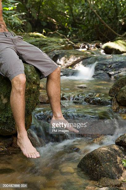Man sitting on rock by stream, low section